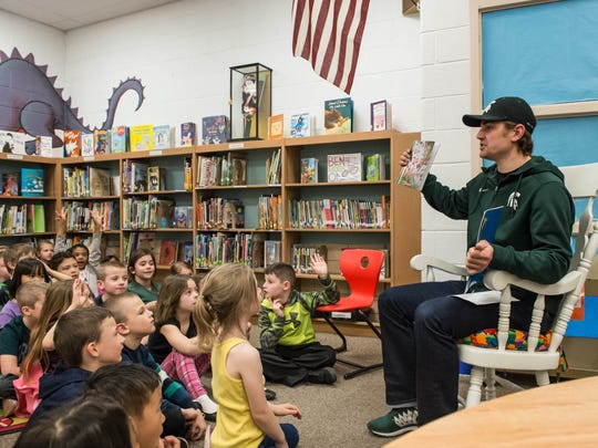 Michigan State University ice hockey player Justin Hoomaian read to students at Riverside Elementary on Tuesday.