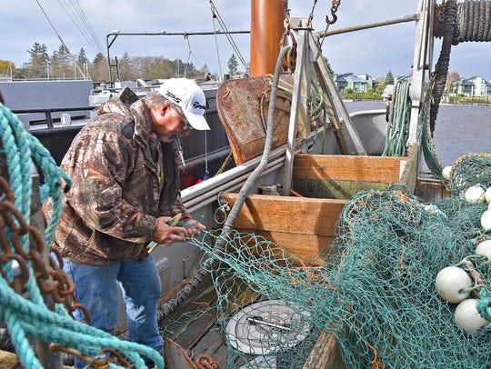 Dave Strickland repairs fishing equipment that he said