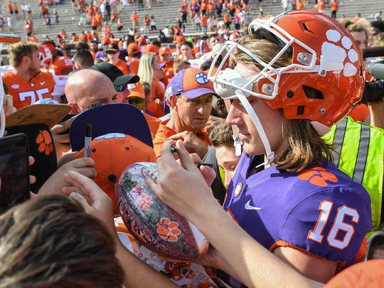 Clemson quarterback Trevor Lawrence (16) signs autographs for children near Clemson head coach Dabo Swinney, middle, after the spring game in Memorial Stadium in Clemson on Saturday, April 14, 2018.