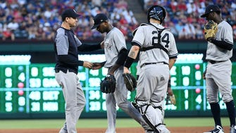 New York Yankees starting pitcher Domingo German hands the ball to manager Aaron Boone as he is pulled from the baseball game against the Texas Rangers in the fourth inning, as catcher Gary Sanchez (24) and shortstop Didi Gregorius, right, stand on the mound Tuesday, May 22, 2018, in Arlington, Texas.