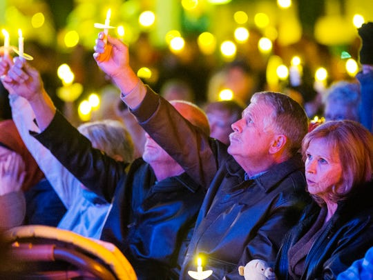 Carl Mueller (middle) holds a candle up toward the
