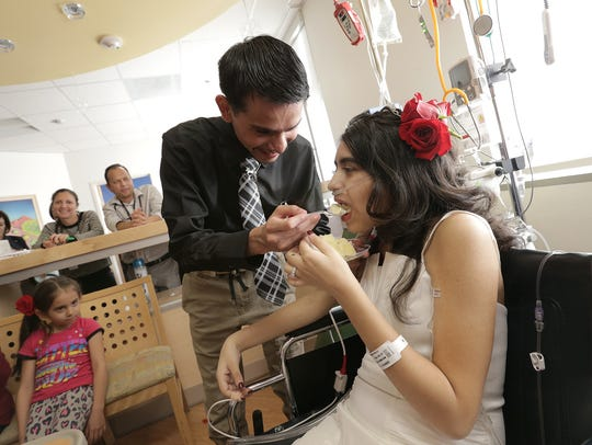 Joshua Ordonez feeds wedding cake to his bride, Lydia Dominguez, Monday at the El Paso Children's Hospital where Dominguez has been in treatment for renal cancer since the age 15. Dominguez has decided to end treatment.