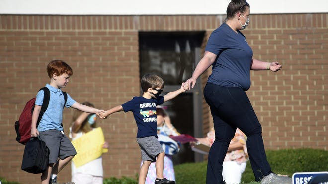 Kids are led to Blue Ridge Elementary School for the first day of classes in Evans, Ga., Monday morning, August 3, 2020.