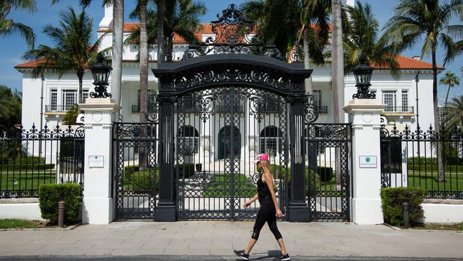 Lisa Johnston of West Palm Beach walks Wednesday along the Lake Trail in front of the closed Flagler Museum.