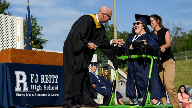 Christopher Kiefer, Vice President of the Evansville Vanderburgh School Corporation School Board Trustees, hands Megan Denise Durre her diploma as she walks across the stage with assistance from EVSC Physical Therapist Kristin Forrest during the Reitz High School commencement ceremony inside the Reitz Bowl, Wednesday, May 23, 2018.