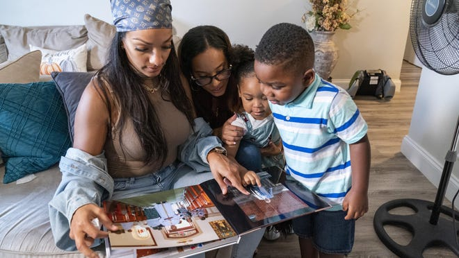 Siblings, from left, Katherine, Jennifer, Jazzmyn and Zavion look at their mother Lunisol Guzman's wedding album, Thursday, Sept. 17, 2020, in Newark, N.J. Four-year-old Zavion and 2-year-old Jazzmyn have been taken in by the oldest of Lunisol Guzman's other three children, Katherine and Jennifer, after she died from symptoms of coronavirus. Lunisol Guzman had adopted them when she was in her 40s.