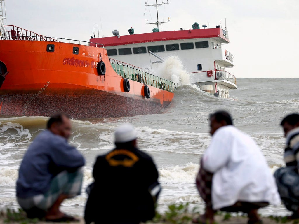 Thai villagers watch a grounded Indonesian tanker from a beach in Narathiwat, Thailand on Dec. 19. The tanker carrying 2.7 million gallons of palm oil ran aground after being hijacked and then recaptured by authorities, officials said.