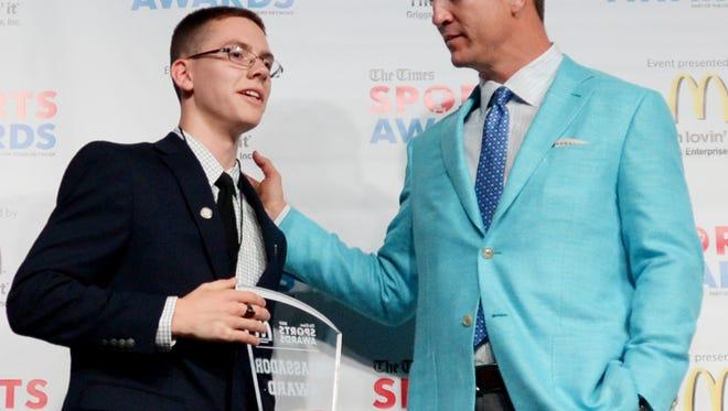 Noah Crofton, a Byrd student awarded the Ambassador Award at the 2017 Sports Award, poses for a photo with Peyton Manning.