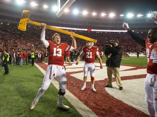 FILE - In this Nov. 26, 2016, file photo, Wisconsin quarterback Bart Houston (13) celebrates with the Paul Bunyan Ax after Wisconsin beat Minnesota 31-17 in an NCAA college football game in Madison, Wis. Axe Week is here for No. 5 Wisconsin, a rivalry game that the Badgers prepare for with intensity even though they have dominated the series with Minnesota over the last decade.(AP Photo/Andy Manis, File)