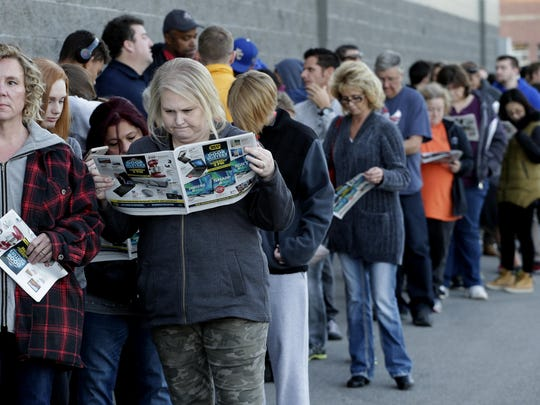 FILE - In this Thursday, Nov. 23, 2017, file photo, people wait in line for a Best Buy store to open for a Black Friday sale on Thanksgiving Day, in Overland Park, Kan. On average, Americans plan to spend more than $550 on gifts for friends and loved ones this holiday season, according to a recent NerdWallet survey conducted by Harris Poll. But budgets are tight. (AP Photo/Charlie Riedel, File)