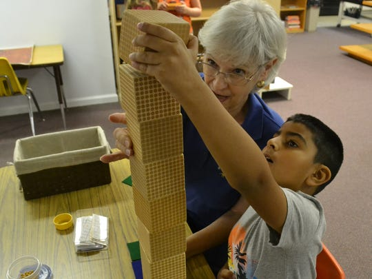 Tejveer Singh, 6, works on counting large numbers with blocks with the help of one of the teachers Deborah Ponder, in the lower elementary class Friday morning.