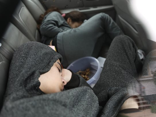 Nicholas Ramos, 15 and his sister, Angelina Ramos, 12, take a nap in their father's car, as the window reflects a home on the street where they used to live.
