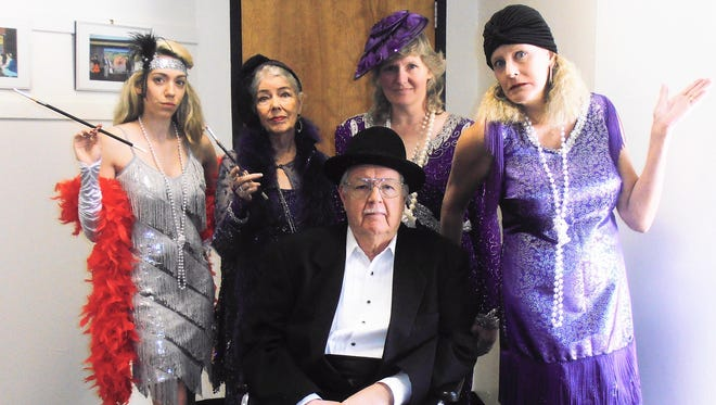 Pictured here are some of the cast of Murder from Beyond, an original murder mystery. From left to right are Miss Ditsy LaRue (Victoria Kennedy), Mrs. Genevieve G. P. S. Morgan IV (Carla Kerr), Delilah Vanderbilt Rockafeller Hearst Gatsby (Kathy Barnes), and Madame LeSue LaRue (Monica Helm). Seated is Da Godfadda (Doug Kerr).