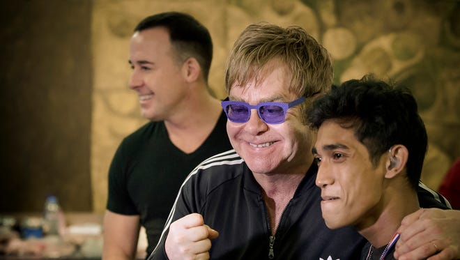 Elton John, center, and husband David Furnish, left, with Euner Neco B. Batan II at a Starkey Hearing Aid fitting In Manila, Philippines.