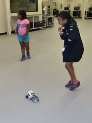 Alyssa Jones does a happy dance as her robot moves around the classroom during a Manufacturing and Coding Academy summer camp at the Strawberry Plains campus of Pellissippi State Community College on Thursday, July 14, 2016. The students are from Project GRAD, the Boys & Girls Club, the Great Schools Partnership and the Emerald Youth Foundation. (J. Miles Cary/Special to the News Sentinel)
