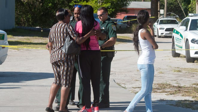 Family members of Alteria Woods, who was killed by a bullet fired from a sheriff's SWAT team member on Sunday, March 19, 2017, inquire about the whereabouts of her body with Indian River County Sheriff's Office deputies in Gifford on Sunday evening.  Authorities were attempting to enforce a search warrant on a known drug house off 45th Street, between 34th and 36th Avenue, when shots were fired from inside the house. Woods was killed in the exchange of gunfire. SWAT team member Deputy Kelsey Zorc was grazed by a bullet, and treated and released from Indian River Medical Center.