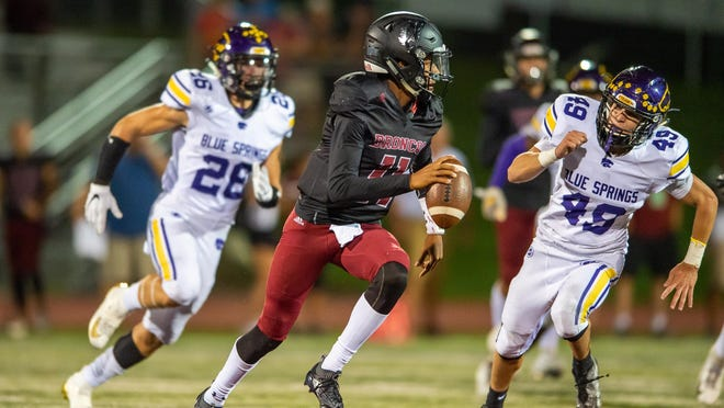 Lee's Summit North quarterback Carlton Perkins, center, scramblling during a game against Blue Springs last season, has experience as the starter, but he will be challenged for the starting job this season by Fort Osage transfer Tre Baker.