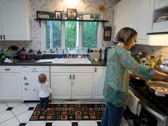 Watts prepares dinner while her daughter Henley plays with magnets May 2, 2016 at her home in Fletcher.