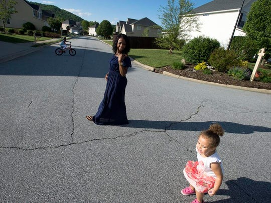 """Leasha Ogle walks down the block from her home in Fletcher with her two-year-old Marjorie as her eldest, Mya, 7, rides her bike Tuesday May 3, 2016. Ogle's PPD set in after the birth of Mya and left her with feelings of failure, loneliness, and sadness. """"I felt too ashamed to even tell my doctor,"""" she said."""