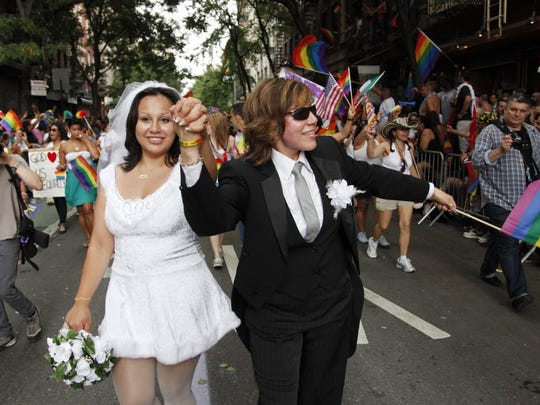 Paola Perez, left, and her partner Linda Collazo, dressed as bride and groom, march in the annual Gay Pride parade in Greenwich Village, Sunday, June 26, 2011 in New York.