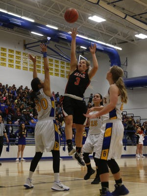 Aztec's Grace Olson shoots a runner over Bloomfield's Alyssa Quintana, left, during the District 1-5A championship at Bobcat Gym in Bloomfield.