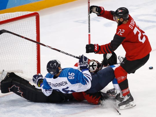 Veli-Matti Savinainen (86), of Finland, collides with goalie Ben Scrivens (30), of Canada, during the second period of the quarterfinal round of the men's hockey game at the 2018 Winter Olympics in Gangneung, South Korea, Wednesday, Feb. 21, 2018. (AP Photo/Jae C. Hong)
