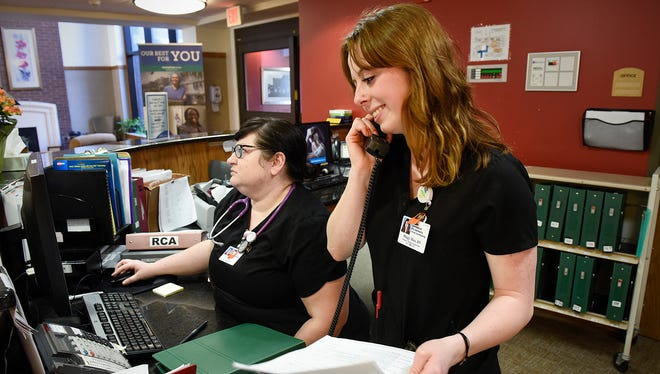 Maggy Hiza, house charge supervisor, handles a phone call while working with Stacy Olson, unit charge, Tuesday, March 7, at CentraCare Health's St. Benedict's Senior Community.