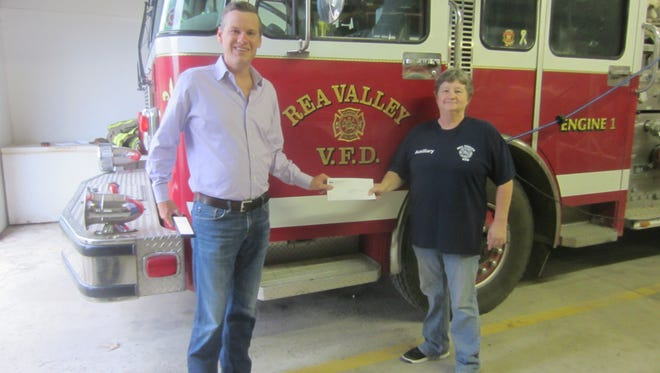 State Sen.Scott Flippo (left)presentsa check to Georgia Jack, President of the Rea Valley Volunteer Fire Department Auxiliary. The check is the result of a grant awarded to the Auxiliary from the Northwest Arkansas Economic Development District Inc.The funds will be used to purchase and install a washer and dryer for the Fire Department. as well as paying for some repairs caused by recent water damage at Station No. 1.