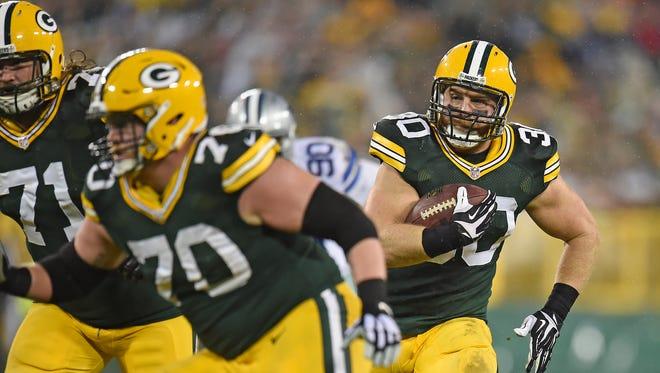 Green Bay Packers fullback John Kuhn (30) runs the ball as guard T.J. Lang (70) and guard Josh Sitton (71) block against the Dallas Cowboys at Lambeau Field.