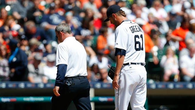 Detroit Tigers pitcher Shane Greene (61) leaves the field with trainer Kevin Rand in the fourth inning of a baseball game against the Cleveland Indians, Sunday, April 24, 2016, in Detroit.