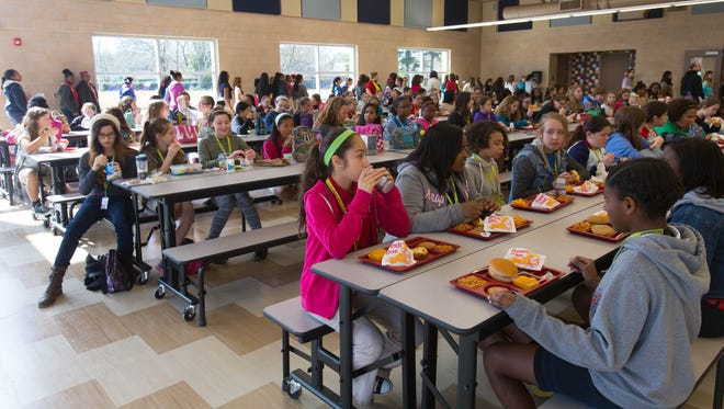 """Students at LJ Alleman Middle School eat lunch in their new """"cafetorium,"""" a combination cafeteria and auditorium, in Lafayette."""