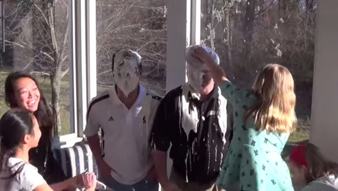 Santa Ono and Brent Cooper take pies to the face to promote reading.