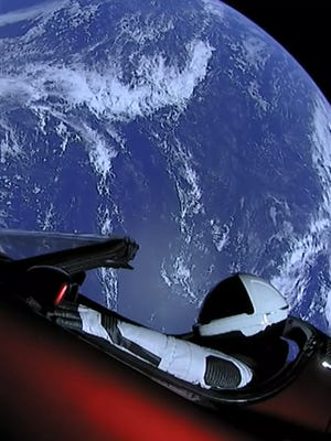 """Starman,"" a mannequin in the Tesla Roadster, floats past the Earth in SpaceX's post-launch live stream."