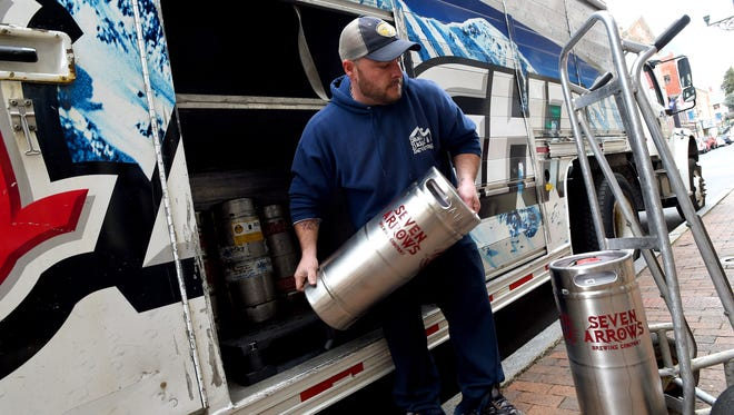 John Lewin of Blue Ridge Beverage unloads two kegs of beer from Seven Arrows Brewing Company while making a delivery to Shenandoah Pizza in downtown Staunton on Thursday, Feb. 12, 2014.