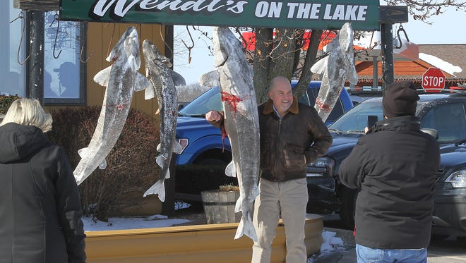 Spectators often pose next to sturgeon outside Wendt's on the Lake between Oshkosh and Fond du Lac along Lake Winnebago during the sturgeon spearing season.
