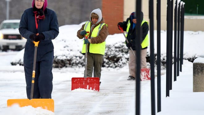 Employees work together to clear sidewalks of snow at Augusta Health in Fishersville on Tuesday morning, Feb. 17, 2015.