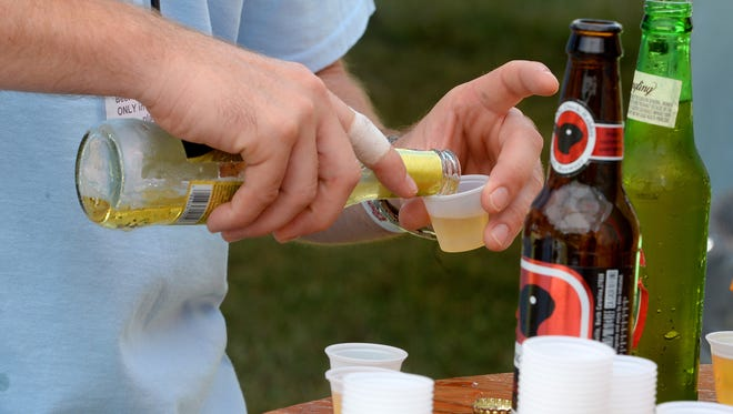 This September file photo shows volunteer Justin Anderson pouring a beer sample for a festival goer near the English farm during Good Times, Tastes and Traditions held at the Frontier Culture Museum.
