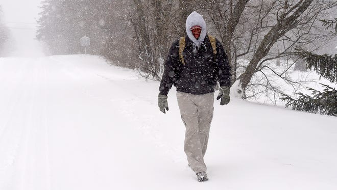 """James Newcomer of Pennsylvania walks through the falling snow along U.S. 11 at Mint Spring on Saturday morning, Feb. 21, 2015. On his way to Texas, he braves the winter weather on his way to a shelter in Roanoke. """"I'm trying to get down there, which probably won't be today,"""" Newcomer says. """"I'll just have to ... maybe build a little igloo or something for warmth tonight."""""""