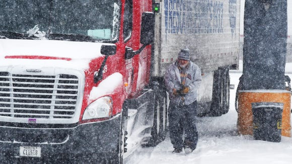 "Snow falls as long distance truck driver Florin Dumitru of Texas walks back to the cab of his truck.  He stopped long enough to fuel up at Pilot Travel Center near Greenville before continuing onward to Illinois on Saturday morning, Feb. 21, 2015.  ""It's so bad. .. It's so bad, I don't know if I can make it because of the weather,"" says Dumitru. ""If you don't need to get out on the roads, stay home.  That's much better."""