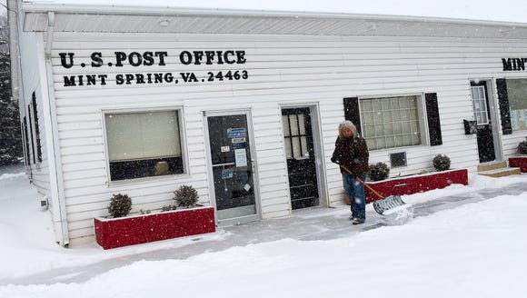 Postmaster relief Anita Fitzgerald shovels snow from