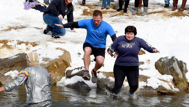 Pastor Randall Black and News Leader reporter Laura Peters jump into the 37 degrees water of the South River during Living Grace MinistriesÕ polar plunge at Ridgeview Park in Waynesboro on Sunday, Feb. 22, 2015. The event served as an incentive for people to donate to the churchÕs mission trip this year to Honduras.