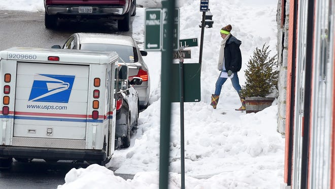 A United States Postal Service mail carrier has to walk through snow covering a sidewalk while making mail delivers along South New Street in downtown Staunton on Thursday, Feb. 26, 2015.