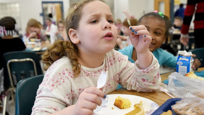 Bite in her mouth, first-grader Leci Stevens  considers the flavor of a piece of cornbread during lunch at William Perry Elementary in Waynesboro on Friday, Feb. 27, 2015. In honor of black history month, the school's parent teacher organization hosted a soul food lunch for students. They served samples of pumpkin pie, cornbread and coffee ice cream.