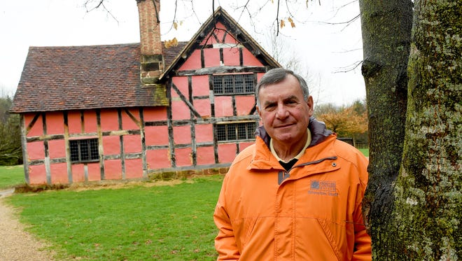 John Avoli, executive director of the Frontier Culture Museum, stands alongside the 1600s English farmhouse on the museum's property in Staunton on Friday, March 27, 2015.