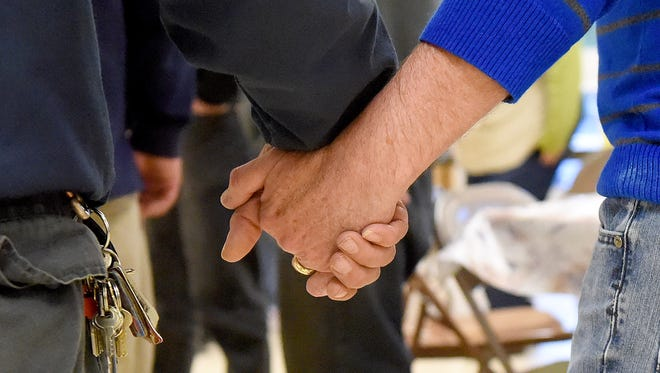 A volunteer clasps hands with a homeless person as a circle is formed for the saying of grace before eating dinner at WARM, operating out of the Fishersville United Methodist Church on Friday, March 27, 2015. WARM is a network of churches operating a night refuge for the Valley's homeless during the coldest winter months.
