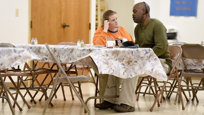"Currently homeless, Amy Roberts sits with her boyfriend, Marco ""Pacman"" Brown, in the fellowship hall of Fishersville United Methodist church after eating dinner on Friday, March 27, 2015.  The single mother spent the night at the WARM thermal shelter, which rotates among participating churches during the winter months. WARM will be reopening its transitional home for homeless mothers like Roberts on May 4."
