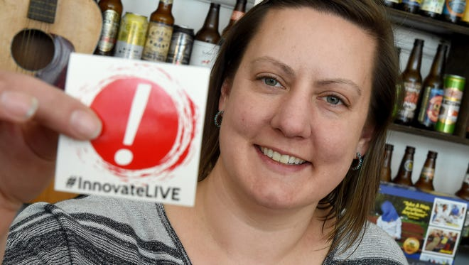 Co-owner of George Bowers Grocery, Katie McCaskey holds up an #InnovateLIVE sticker advertising the new Innovate Live Festival while at work on Wednesday, April 1, 2015. McCaskey will be one of the speakers at the three-day event  which starts April 24.