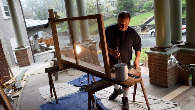 Tim Steele of Sevenodd Inc. can hear the rain fall behind him as he dips his brush into the can of paint. He paints window screens one at a time on the front porch of a residence on North Lewis Street in Staunton on Tuesday, April 14, 2015.