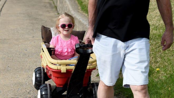 Three-year-old Miah Pforr of Waynesboro rides in her little red wagon. Her grandfather George Pforr of Stuarts Draft pulls her alongside Ivy Street in Waynesboro on Wednesday, April 29, 2015.