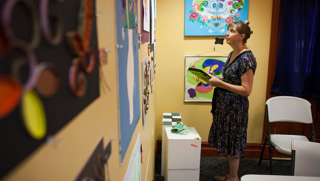 "Rebecca Textor, a Regional Suicide Prevention Coordinator with Northwester Community Services looks at works of art during the ""Art: Recovery through the Seasons, works by consumers of mental health services"" show on Friday, May 8, 2015."